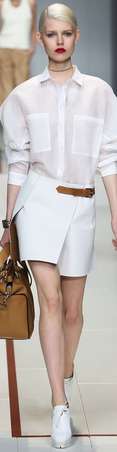 Style: Sheer shirt with a structured skirt, reinforces the contrast between femininity and masculinity.