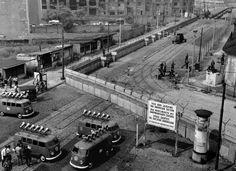 """Lautsprecherwagen-Kolonne des """"Studios am Stacheldraht"""" an der Sperrmauer Stresemann- Ecke Niederkirchnerstraße, im Vordergrund viersprachiges Sektorenschild, mit dem die US-Amerikaner besonders ihre Viermächteverantwortung für die ganze Stadt betonten, im Hintergrund Ruine des Hauses """"Vaterland"""" am Potsdamer Platz 28. Juli 1962"""