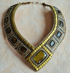This necklace is a handmade embroidery.  It has been made with Japanese Toho seed beads,tila,Swarovski crystals and natural Tiger Eye.  The back side of the necklace and earrings cover with natural leather.  Necklace 22 /55 cm  100% handmade  Made with love  Necklace packed in a gift