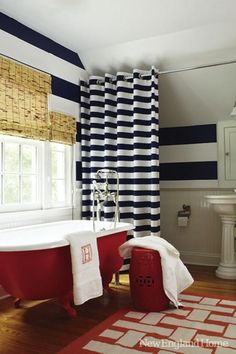 Cute boy's bathroom with red claw foot tub, glossy red garden stool, white & red basketweave rug, glossy white pedestal sink, white & blue stripe shower curtain, white & blue horizontal stripe walls, chair rail and beadboard backsplash and bamboo roman shades.