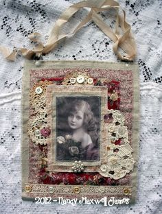 A gorgeous fabric collage made from fabric, vintage laces, mother of pearl buttons, beads, and a fabric image.