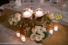 Small rose arrangements placed around floating candles.