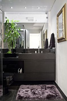A bancada do lavabo é de granito preto absoluto fosco, da Mont Blanc Mármores e Granitos. Louças e metais são da Deca