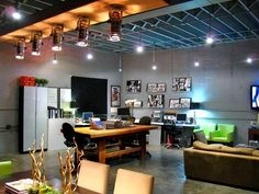 industrial spotlights and track lighting illuminate this modern loft living room which has concrete floors office space a neutral sofa green armchairs awesome office spaces