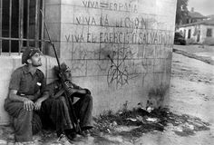 Gerda Taro: Two Republican soldiers in front of wall with rightist slogans and symbols, Battle of Brunete, Spain, 1937.