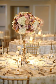 Gold candelabra centerpiece with gorgeous flower arrangement.