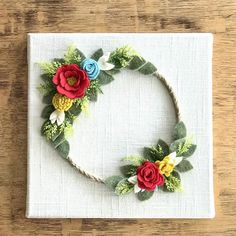 This listing is for a Felt Flower Wreath wall hanging. An art canvas is covered in cotton linen fabric and then hand cut wool felt flowers and leaves are added layer by layer. This 10x10inch wall hanging would be a great addition to nursery, bedroom, entryway or door. It would also make a