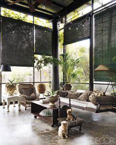 Preciosa decoración de salón con estores de bambú, cojines de tela africana, mesa de yeso y el suelo de hormigón de color, un ambiente de lo mas exótico