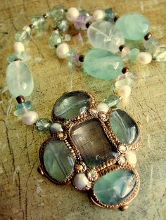 Hand-made costume jewelry in Byzantine - Medieval style.  Center stone is fluorite, surrounded with fluorite beads and fresh water pearls. Chain is made from threaded fluorite beads, fluorite chip beads, fresh water pearls, and Czech fire-polish glass beads.