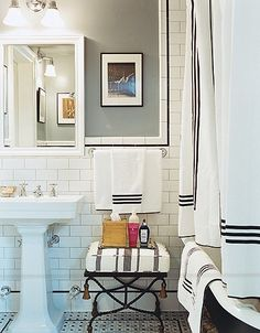 I love this modern but still vintage type bathroom. It feels very European to me. Note thin black stripe on top and bottom. White mirror. Medicine cabinet?