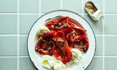 A plate of roasted piedmont peppers on an enamel plate with halved balls of mozzarella, alongside an opened tin of anchovy fillets on a tiled worktop.