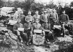 """Dansksindede sønderjyder, som var tvangsudskrevet som tyske soldater. Her fotograferet et sted i de baltiske lande på østfronten, 1914-18. På skiltet: """"En hilsen sender 12 Nordslesvigere fra Skyttegraven i Kurland."""""""