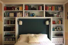 Bookshelves surrounding bed + dark headboard + sconces = cozy nook.