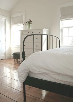 Simple black and white farmhouse bedroom with wood floors