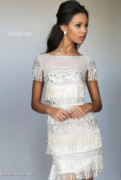 Sherri Hill 50541 is a 1920's inspired short sleeved short homecoming dress with fringed tassels and vibrant beadwork.