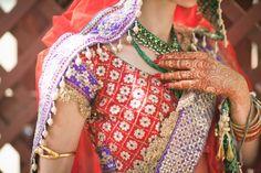 Indian bride in red and purple Tarun Tahiliani bridal lehnga and green wedding jewelry