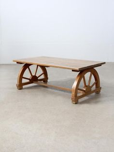 """A 1940s vintage Monterey style coffee table. The wood table features a faux bois finish, """"plank"""" top, and wagon wheel shaped legs. wood table with faux bois finish blonde tone wagon wheel shaped legs plank top unmarked CONDITION In good, sturdy condition. There is wear to the painted finish on the table top, and minor scratches and nicks in the wood, particularly on the bottom cross board. MEASUREMENTS Height 13.75 inch 34.9 cm Length 36 inch 91.4 cm Width 20 inch 50.8 cm ..."""