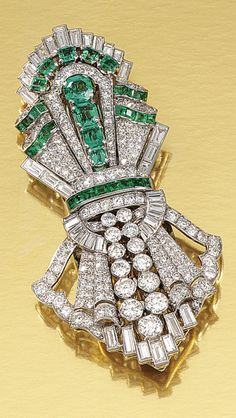EMERALD AND DIAMOND DOUBLE CLIP BROOCH, 1930S.  Each clip of geometric design embellished with stylised scroll motifs, set with circular-, single-cut and baguette diamonds, further accented with lines of step- and calibré-cut emeralds, fitted case.