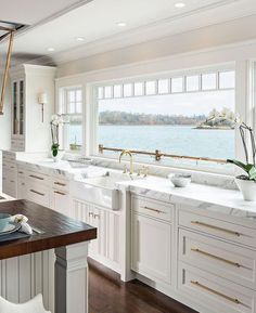 Stylish lakefront home with all white kitchen, marble countertops, and brass har. - Stylish lakefront home with all white kitchen, marble countertops, and brass hardware accents - Sweet Home, All White Kitchen, Classic White Kitchen, White Marble Kitchen, Marble Wood, Lakefront Homes, Beach House Decor, Home Decor, House On The Beach