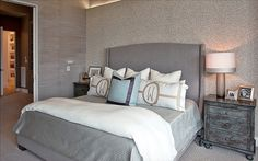 modern-bedroom-features-gray-bed-with-wingback-headboard-and-monogramming-pillows_silver-textured-bed-sheet_white-throw-blanket_rustic-side-cabinets_modern-table-lamp_beige-sandy-texture-wall_beige-textured-rug.jpg (870×545)