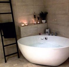 Bathroom - love the towel ladder and the corner setup/shelving. I don't love the tub.