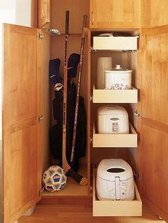 Sturdy roll-out drawers hold appliances used only occasionally, like the slow cooker and bread machine. A vertical cabinet provides room for tall items--brooms, mops, and Aaron's hockey sticks. (Photo: Photo: Emily Minton Redfield; Stylist: Lydia DeGaris Pursell)