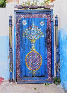 door. painted wood. baroque? middle eastern? mediterranean? colour. cob. entrance.