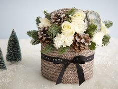 Jane Packer  - Blizzard, £65.00 (http://www.janepackerdelivered.com/blizzard/)  This Christmas hatbox design is chic and contemporary in white and grey. Large white roses, carnations, snowy pine cones and fragrant pine foliage are encased in a soft grey hatbox with the addition of a unique succulent plant.