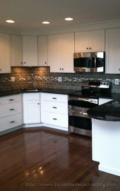 Sleek stainless steel appliances and modern tile #backsplash.