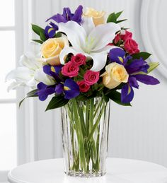 FTD® proudly presents the Vera Wang New Day Dawns™ Bouquet. A colorful burst of roses and iris form a charming bouquet of spring sophistication and timeless elegance. Pale yellow roses, deep purple iris, fuchsia spray roses and white Oriental lilies are brought together to create stunning flower bouquet set to capture their every attention. Presented in a modern clear glass vase.