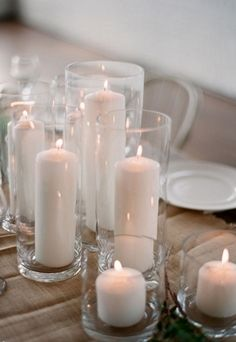 A variety of white candles in glass holders is a budget-friendly way to decorate your wedding.