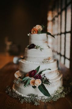 Gorgeous wedding cake lined with burgundy and coral roses | Image by Love Stories by Halie and Alec
