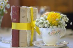 Yellow vintage tea cups filled with yellow flowers Vintage style summer Tea Party Tea cups wedding style table decor Pastel blooms and old vintage books covered in lace and ribbon contact www.blushrose.co.uk Manchester wedding flowers