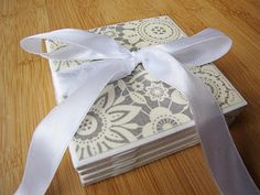 coasters made from inexpensive tiles, craft paper, mod podge, and cabinet door stops...cute!
