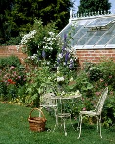 Traditional small metal table and chairs in an English walled country garden with flower border