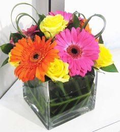 57MT Pink and Orange Gerbera, Yellow Roses in leaf lined cube vase.