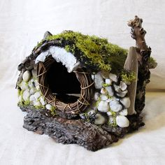A lovely little hobbit house for the wee folk! This charming little cottage has been built around a small grapevine wreath that forms the classic round hobbit like door. The front wall has been constructed from quartz river pebbles. Pieces of driftwood and branches shore up the sides and extend over the roof of the house, suggesting a chimney or two. The roof has pinecone shingles and mossy growth while a unique bark outcropping tops off the doorway, inviting the fae to explore inside. The…
