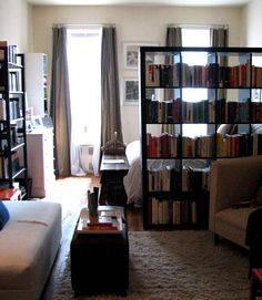 """I like how this bookcase from Ikea is used to divide this studio apartment up into two different sections. I can see myself doing something like this in my son's room (as they share) to give them each a sense of """"privacy""""."""