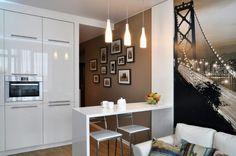 A kis kétszobás, 39.6 négyzetméteres lakás kellemes, otthonosan modern berendezése és dekorációja alapvetően a fehér szín és a meleg, természetes barna árnyalatok kontrasztjára épít. Az egyik helyiség a nappali, konyha egyben, étkezéshez egy kis szimpla bárpult ad helyet két személynek - a pult egyben a pihenő zónát vizuálisan is elválasztja a konyhától.