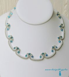 Beadwoven necklace by Susan-Design. She says that this delicate piece was shaped into a curve by changing the white beads from 11/0 to 15/0. Silver beads are 11/0 everywhere. The accents are Swarovski Indicolite AB2x bicones.