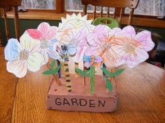 Cover a block of foam with brown paper for dirt. Color and cut out flowers. Glue to green painted popscicle sticks and add leaves. Stick into the foam. We added a bee,a butterfly, a sun and several raindrops to the garden for the letter G.