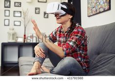 Woman touching something using virtual reality headset glasses and sitting on the couch