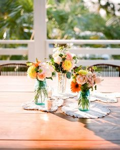 For an outdoor reception in Santa Rosa Beach, Florida, a collection of vintage bottles, jars, doilies, and mercury glass votives decorated the tables. Blooms in soft, muted corals, peaches, pinks, whites, and ivories completed the centerpieces.