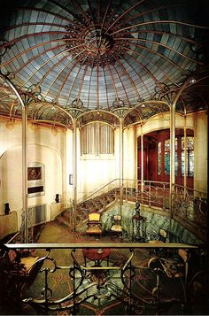 Art Nouveau Salon of Hotel van Eetvelde in Brussels, Belgium. Plain cream colored walls, decorative ironwork and stained glass, marble wall