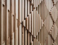 facade made up of wooden pieces that form a three-dimensional diamond pattern