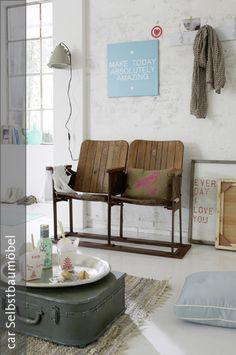 Erstaunlich, wie gut sich Vintage-Stücke vom Flohmarkt in der Wohnung machen können, wenn sie richtig kombiniert werden. Der Koffer wurde zum Möbel umfunktioniert und fungiert nun als unkonventioneller Tisch, um den man sich knien kann. Auch die alten Kinostühle verbreiten einen modischen 20er-Jahre-Charme und wirken in Kombination mit farbigen Wandbildern und einer weißen Mauerwand sehr lässig.