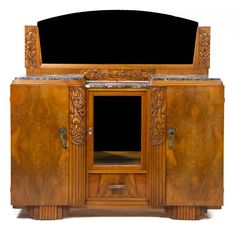 A French Art Deco Walnut Dining Suite, comprising an extension table with two leaves, two marble top sideboards and a mirror, each with carved fruit decoration and six side chairs.