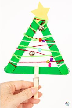 Yarn Wrapped Musical Popsicle Stick Christmas Tree Craft for Kids - Create this easy Christmas Ornament with your kids this Christmas. The Christmas Tree craft doubles up as a jingly musical instrument that will be fun going all day long. Christmas Tree Yarn, Easy Christmas Ornaments, Christmas Tree Painting, Christmas Crafts For Kids To Make, Colorful Christmas Tree, Preschool Christmas, Christmas Activities, Easy Crafts For Kids, Kids Christmas