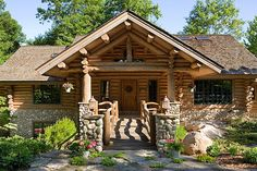 I love the stone work on this log cabin. Beautiful entry.    Handcrafted red pine logs, bolstered by stonework, a custom door and two 22-foot log beams supporting the king-post porch truss create a rustic look.