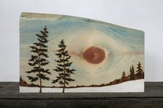 The two trees in this original wood burned art gently sway in the breeze at the fields edge. A knot in the wood creates a sun and casts a warm